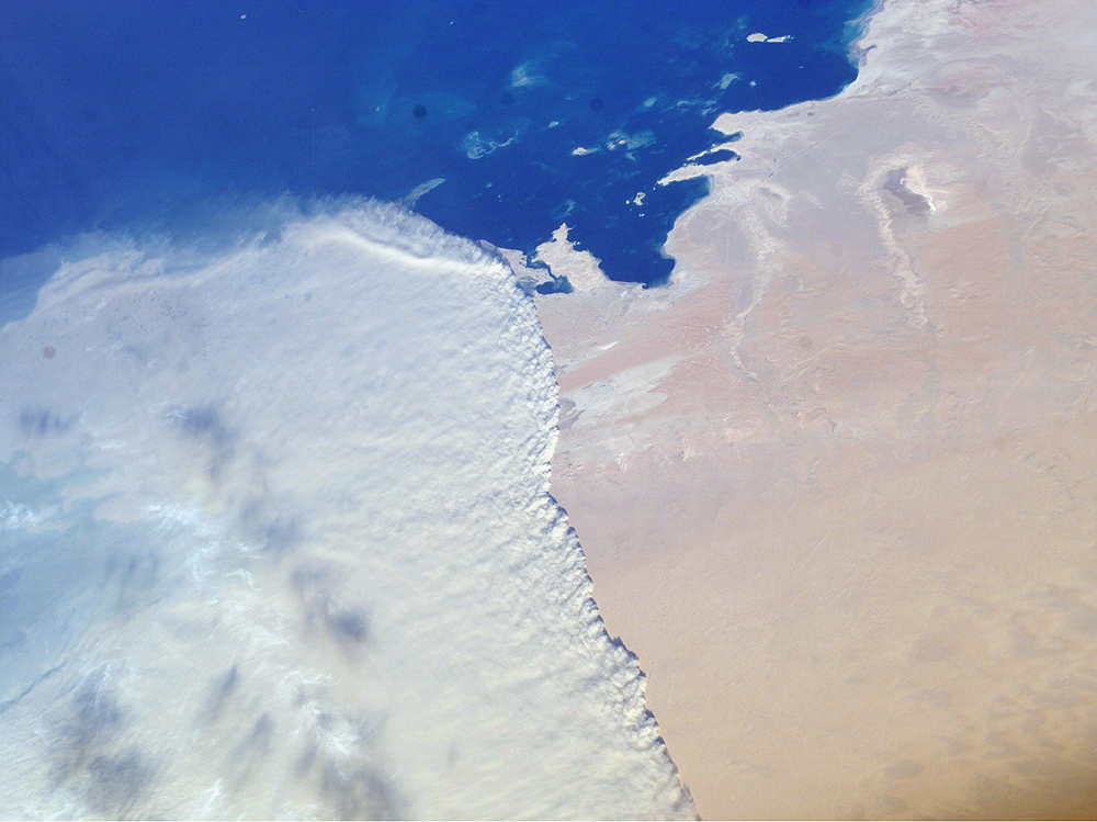 This striking photograph shows a massive sandstorm sweeping over the Persian Gulf state of Qatar as it races southward toward southeastern Saudi Arabia and the United Arab Emirates on February 15, 2004. A major upper-level, low-pressure system over southwestern Asia led to a series of storms sweeping through the area. The crew of the International Space Station acquired this image with a digital camera using a 50-mm lens.