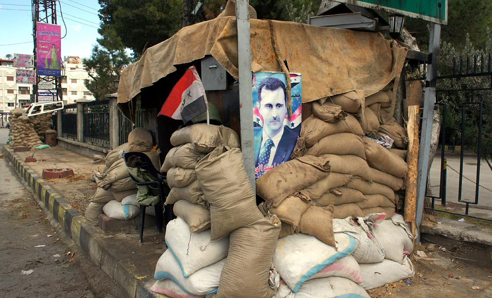 Hunkering down: a poster of Syria's president at a checkpoint on the outskirts of Damascus, Jan. 14 2012. Photo taken by VOA Middle East correspondent Elizabeth Arrott while traveling through Damascus with government escorts.