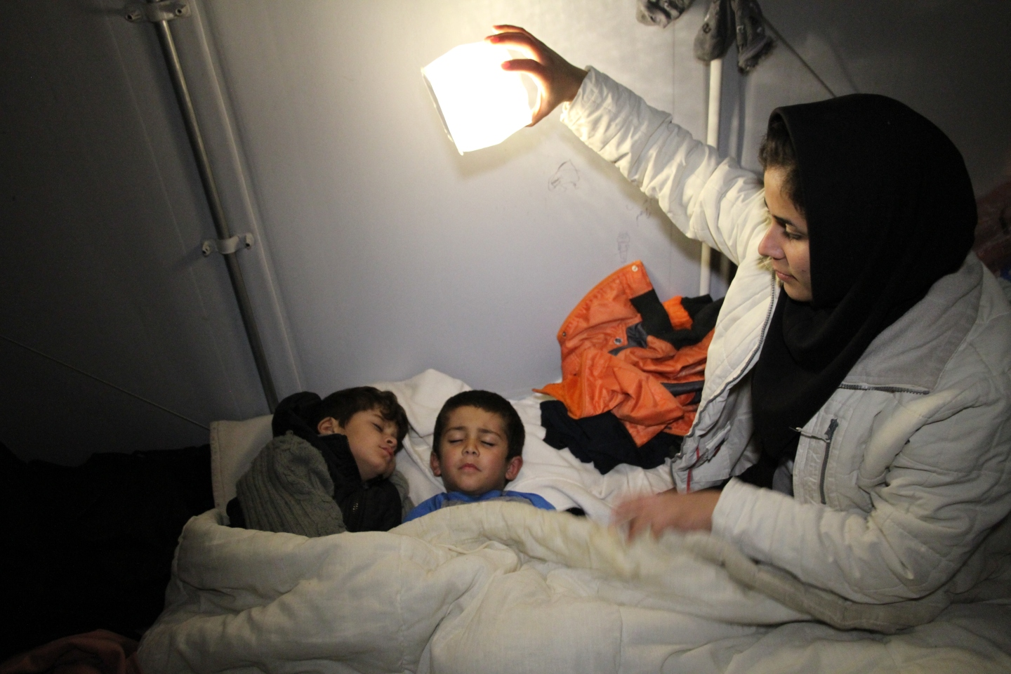 Dr. Alison thompson delivering light with a solar lamp at a refugee camp