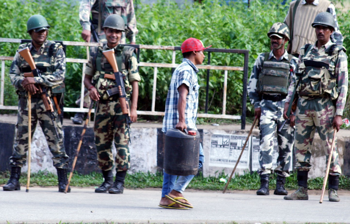 Indian soldiers of the CRPF Team and Assam police officers secure a street, as a Boy carries a Foul, during Garo National Council (GNC) Indefinite Bandh, Monday, In Paikan NH-51 and NH-37. (Pictures by Vishma Thapa)