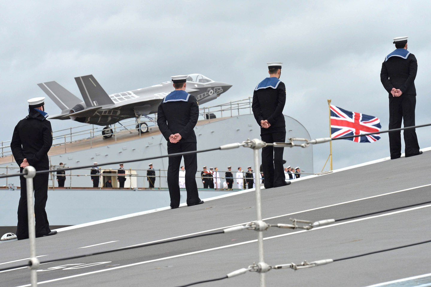 Pictured are events from the Queen Elizabeth naming ceremony conducted at Rosyth Dockyard. Pictured are Royal Navy Personnel aboard HMS Queen Elizabeth with an F-35B Aircraft in the background. Her Majesty The Queen officially named the UK's newest aircraft carrier at Rosyth, near Edinburgh, in a spectacular ceremony celebrating British Naval capability. The Prime Minister, Secretary State of Defence and the First Sea Lord joined the celebrations, along with allies from around the globe and more than 3, 500 people involved in the design and construction of the largest warship ever built in the UK. Organization: Royal Navy Object Name: MR140096098 Category: MOD Supplemental Categories: Carriers, Ships, Equipment, Royal Navy, People Keywords: Officer, Rating, Male, Sailor, Non-Identifiable, Personnel, Scotland, Clyde, HMNB, Dockyards, Union Jack , Queen Elizabeth, CVS, Aircraft Carrier, Rosyth, Naming Ceremony, Royal Navy, Ship, Carrier, CVF, Queen Elizabeth Class, QE Class, HMS Queen Elizabeth, R08, Royal Air Force, RAF, Combat, F-35B, Lightning II, Joint Strike Fighter, JSF Country: UK