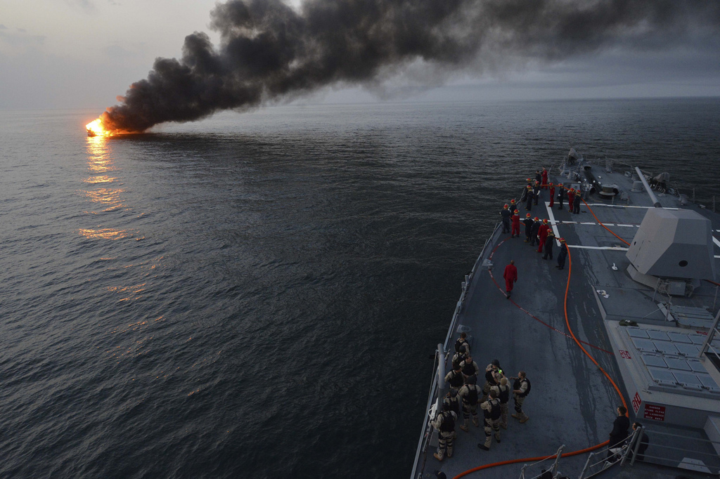 U.S. Sailors aboard the guided missile destroyer USS William P. Lawrence (DDG 110) prepare to offer rescue assistance to a burning vessel March 11, 2013, during a transit in the Strait of Hormuz. The William P. Lawrence was deployed to the U.S. 5th Fleet area of responsibility to promote maritime security operations, theater security cooperation efforts and support missions for Operation Enduring Freedom.