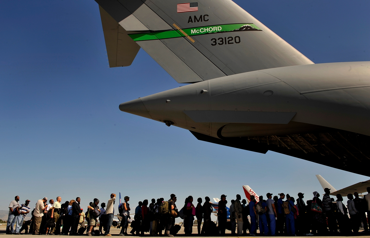 Haitian evacuees wait to board a U.S. Air Force C-17 Globemaster III aircraft at the Toussaint L?Ouverture International Airport in Port-au-Prince, Haiti, Jan. 28, 2010. During the flight, more than 100 Haitians were evacuated to a transition center in Orlando, Fla. The Department of Defense and the U.S. Agency for International Development are conducting the operation to provide aid and relief to Haitian citizens affected by the 7.0-magnitude earthquake that struck the region Jan. 12, 2010. (DoD photo by Staff Sgt. Clay Lancaster, U.S. Air Force/Released)